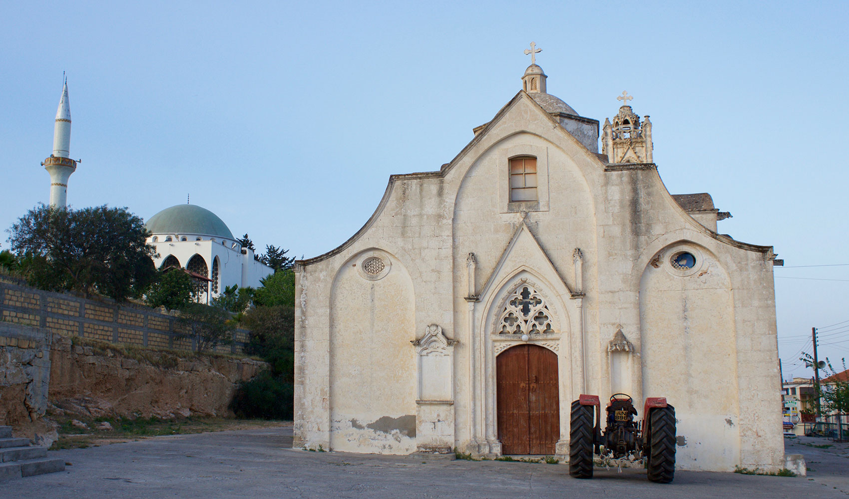 Greek Orthodox church sits near a Muslim mosque in the town of Rizokarpaso